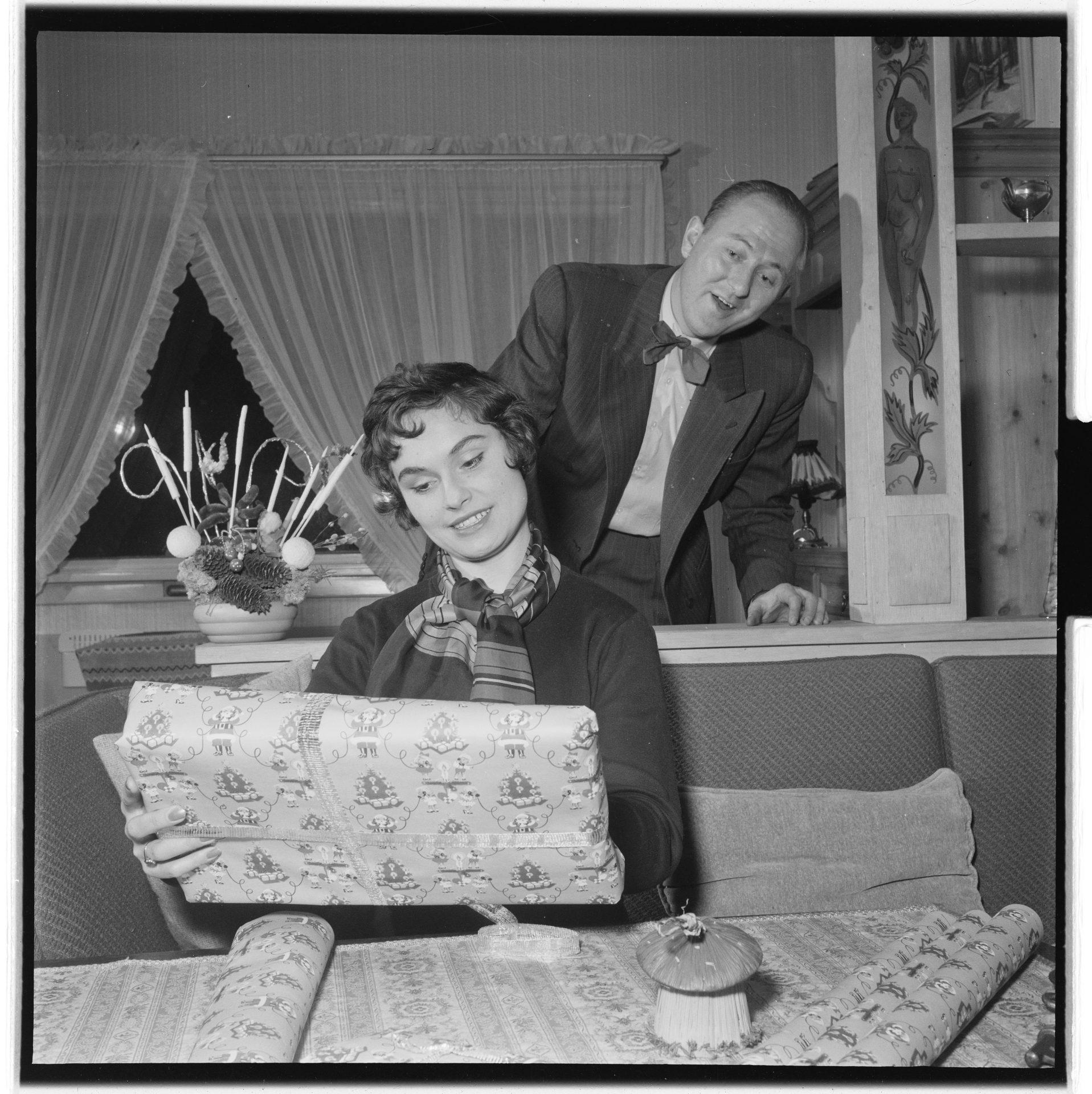 Ei kvinne opner ei julegåve medan ein mann står bak og ser på. Foto.